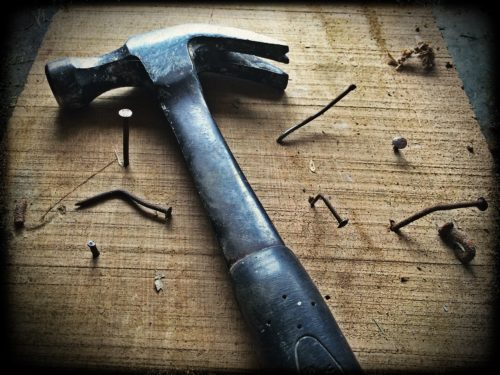 black-claw-hammer-on-brown-wooden-plank